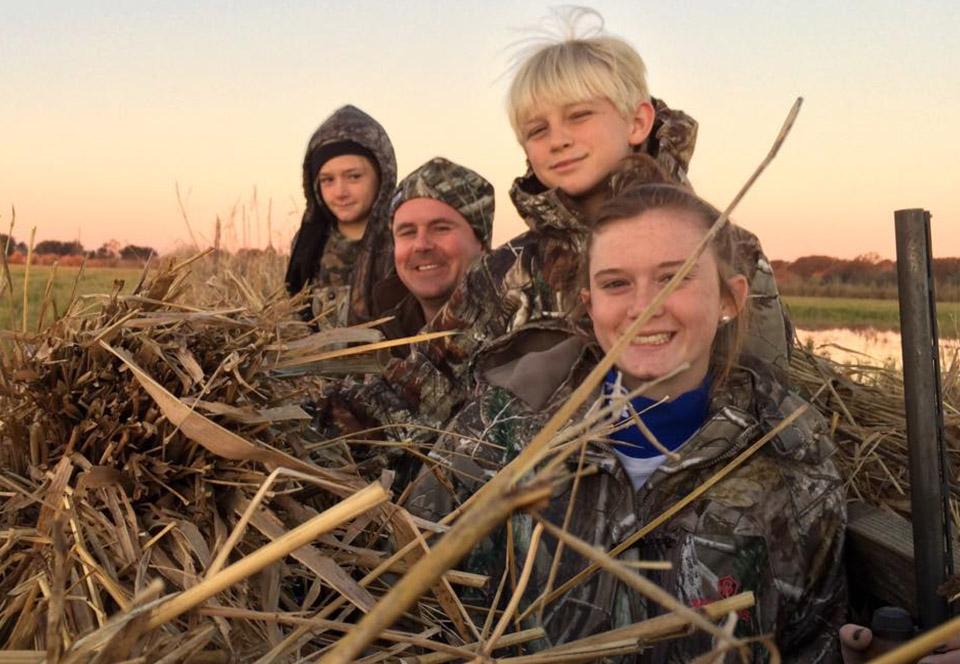 Beau Beaullieu and his children smile together in a duck blind.
